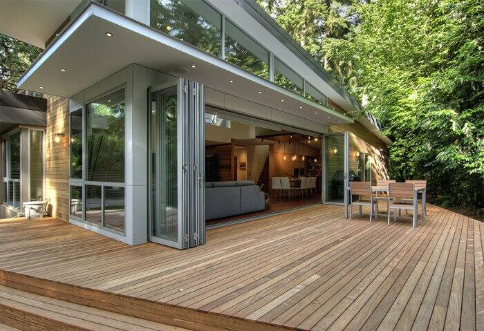 Large Folding Patio Doors Stacked Against Each Other Leading To Deck With Outdoor Dining Table
